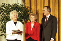 Former First Lady Betty Ford receives the Presidential Medal of Freedom from President George H.W. Bush and First Lady Barbara Bush. November 18, 1991.