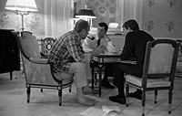 President Ford, in his pajamas, meets with staff members Steve Todd (military aide) and Terry O'Donnell in the President's suite in the Akasaka Palace, Tokyo, Japan.