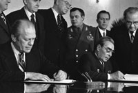 President Ford and Soviet General Secretary Leonid I. Brezhnev sign a joint communiqué following talks on the limitation of strategic offensive arms. The document was signed in the conference hall of the Okeansky Sanatorium, Vladivostok, USSR. November 24, 1974