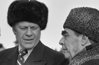 President Ford dons a Russian wool cap upon his arrival in Soviet Union, shown here with Soviet General Secretary Leonid Brezhnev at Vozdvizhenka Airport, Vladivostok, USSR.  November 23, 1974