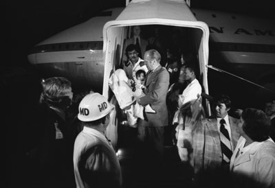 "President Ford carries a Vietnamese baby from ""Clipper 1742,"" one of the Operation Babylift planes that transported approximately 325 South Vietnamese orphans from Saigon to the United States."