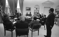 Secretary of State Henry Kissinger interrupts a meeting with senior advisers to relay the latest information on the U.S. evacuation of Saigon.  Oval Office.  April 29, 1975.