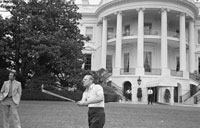 President Ford practices golf on the South Lawn of the White House under the watchful eye of the Secret Service.  May 9, 1975.