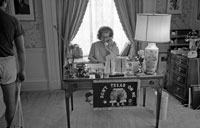 "First Lady Betty Ford works at her desk in the East Wing, where a ""Don't Tread on Me"" ERA doormat hangs from the front of her desk.  June 30, 1975."