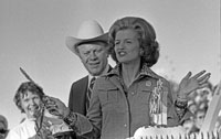 President Ford stands by as First Lady Betty Ford prepares to cut the birthday cake at the dedication ceremony for the Oklahoma State Fair Grounds' Independence Arch and Constitution Fountain.  Oklahoma City, Oklahoma.  September 19, 1975.