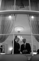 President Ford and Egyptian President Anwar Sadat look out the window of the Yellow Oval Room during a pre-State Dinner reception.  October 27, 1975.