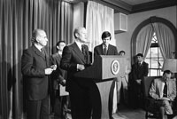 President Ford makes remarks to the press announcing the national Swine Flu Immunization Program.  Also shown are Center for Disease Control (CDC) Director David J. Sencer (to Ford's left) and Secretary of Health, Education and Welfare F. David Mathews (to Ford's right).