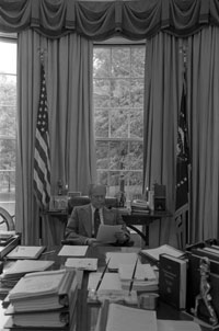 President Ford studies a speech during a meeting with his editorial staff. Oval Office . May 1, 1976.