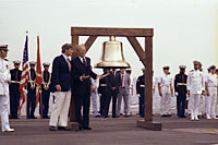 President Ford initiates the ringing of Bicentennial bells across the nation while on the flight deck of the USS Forrestal with Bicentennial Administration head John Warner in observance of Operation Sail activities in New York Harbor.