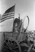 President Ford boards the Michigan wagon at the Bicentennial Wagon Train Pilgrimage encampment, where covered wagon trains converged after crossing the nation on historical trails.  Valley Forge State Park, Valley Forge, Pennsylvania.  July 4, 1976.