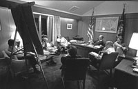 White House Chief of Staff Dick Cheney comments during a campaign strategy session at Camp David. (Counterclockwise from President Ford are his son Jack Ford, Counselor John Marsh, Robert M. Teeter of Market Opinion Research Corp., President Ford Committee Deputy Chairman for Political Organization Stuart Spencer, Cheney, and Counselor and speechwriter Robert Hartmann.) August 6, 1976.