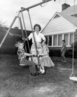 Betty watches as her children Steve and Susan ride on a glider in the back yard of their home at 514 Crown View Drive, Alexandria, Virginia. Her son Michael appears in the background. 1962.