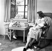Betty holds second son Jack Ford while eldest son Michael plays a t a small table in their apartment at 1521 Mount Eagle Place, Alexandria, Virginia. 1952.