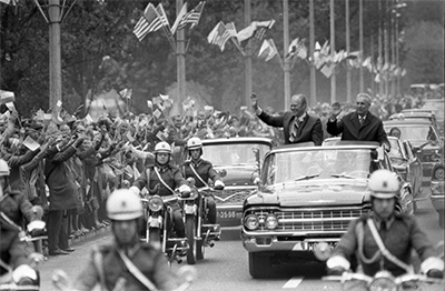 President Ford and Edward Gierek, First Secretary of the Central Committee of the Polish United Workers' Party, wave to the crowd from their car in the motorcade from Okecie International Airport to Wilanow Palace in Warsaw, Poland.