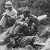 A grief stricken American infantryman whose buddy has been killed in action is comforted by another soldier. In the background a corpsman methodically fills out casualty tags, Haktong-ni area, Korea., 08/28/1950