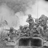 Vietnam....Marines riding atop an M-48 tank cover their ears as te 90mm gun fires during a road sweep southwest of Phu Bai., 04/03/1968