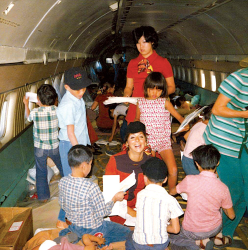World Airways flight attendants Carol Shabata (standing) and Valerie Witherspoon (kneeling) play with the Vietnamese orphans on the historic evacuation flight.